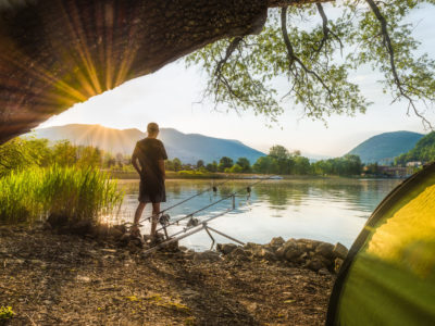 Fishing adventures, carp fishing. Angler, at sunset, is fishing with carpfishing technique. Camping on the shore of the lake