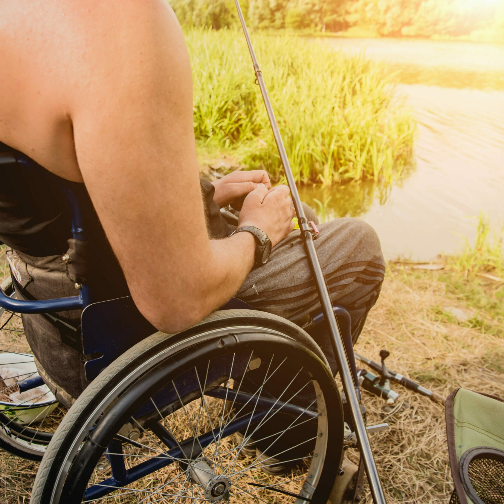 Handicapped man fishing at a lake. Wheelchair. Camping. Summertime
